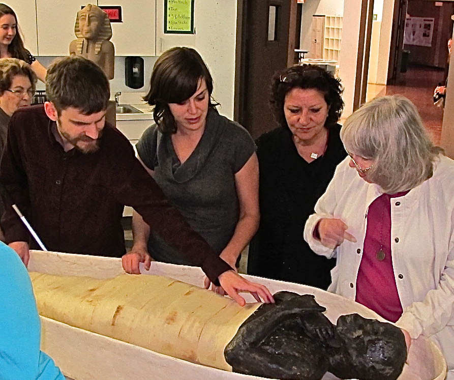 Maria, second from the left, showing members of Philly Touch Tours' team the replica mummy